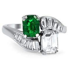 This absolutely stunning Retro-era ring features an emerald cut diamond and a gorgeous green emerald, with ten diamond baguette accents flush set into the curving white gold band