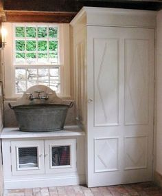 I only thought I loved my laundry room, until I saw this one.  Everything about this custom space is visually stunning to me (who cares if it's not 100% practical!) – the raised diamond pattern door hiding a stacked set, a metal wash tub sink with arched marble backsplash, chicken wire on the base storage cabinet, old brick flooring and wooden beams.
