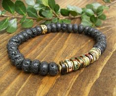 Mens Stretch Bracelet, Black Lava Stone, Earthtone Greek Ceramic Heishi Beads, Gold, Rustic, Elegant, Unisex, Casual Jewelry, Gift Idea  Casual yet elegant - rugged yet refined.  This unisex bracelet combines the rugged nature of black lava rondelle beads with sleek and beautifully colored Greek ceramic beads. The ceramic beads are multi-colored in muted tones of brown, green, maroon, gold, and terracotta. They are separated by gold-plated (over brass) slim faceted spacer beads. This is a…