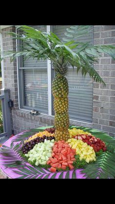 Decorando con piñas la mesa de las frutas.