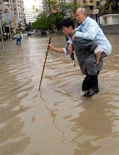 A young man helps an elderly manacross a flooded street after heavy rain