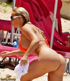 Nicole Coco Austin in an orange bikini reaching for something while her huge butt is exposed.