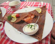 A smoked salmon galette dinner in Rennes. Brittany is the home of crepes in France and the buckwheat variety - galettes - work with an almost endless variety of ingredients. Behind the plate is a traditional Bretton cidre cup, the proper way to drink another Bretton specialty, lightly fermented apple cider.