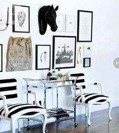 Modern gallery wall featuring black and white art prints and objects like a black horse head and a wishbone. Love the bar cart as a side table and the white painted chairs covered with a wide black and white stripe fabric in this entryway - Eclectic Gallery Art Wall Ideas
