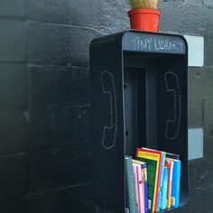 """Pay phone booth repurposed as a tiny library – a """"take a book, leave a book"""" little library."""