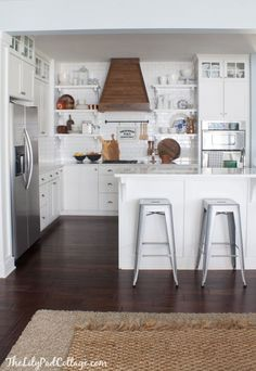 White kitchen with open shelving and a beautiful Wood Range Hood - The Lilypad Cottage