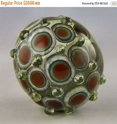 a round transparent focal with layered dots in reactive colors handmade lampwork glass bead