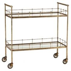 """Wheeled bar cart with two tier shelves.   Product: Serving cartConstruction Material: Iron and mirrored glassColor: GoldFeatures:   Two tiersSits on casters for mobilityAntiqued mirrored borders Dimensions: 33"""" H x 33"""" W x 32"""" D"""