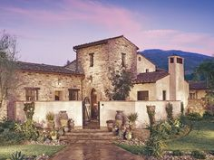 Tuscan stone and stucco exterior with stucco wall surrounding entry courtyard