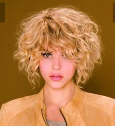 Short curly hair cut shorter at the back and longer at the front in a rich warm autumn blonde.