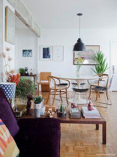 Sala de jantar iluminada com mesa redonda e cadeiras de diferentes modelos.