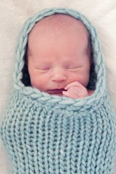 baby boy in a blue cocoon.  Natural light.  cocoon knitted by his grandma. photo by jilldimassimophoto.com