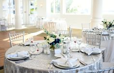 Silver table overlays. Wedding reception. Glam. Elegant. Silver chargers. Silver chiavari chairs, diamond napkin rings.