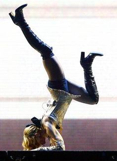Madonna performs yoga manoeuvres on stage.