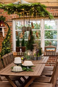 .Christmas greenery in an outdoor chandlier. Stars, blubs and pine cones could be used on my antler chandlier.