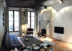 View of the living room with its fireplace in trompe l'oeil and flatscreen television - Marais Apartment Rental