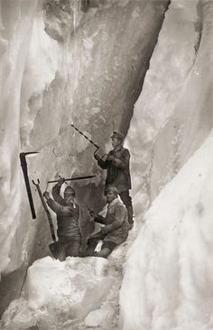Vintage picture of three soldiers drilling into the ice on the mountain.
