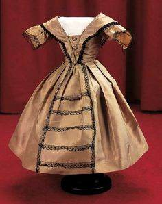 Of rich bronze-green silk,the gown has a low-cut dart-shaped bodice with wide bretelles edged in black tatting,flared short sleeves with black Alencon lace that is repeated on the skirt front; with self-piping at edges of bodice,self-covered buttons,box- pleated skirt. French,1860s.