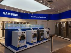 """Laundry and kitchen appliances on display underneath Samsung's """"Smart"""" home appliances branding."""