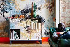 Divisão com parede e módulo de arrumação a combinar, personalizados com o quadro PREMIAR inspirado na natureza. Homem a descansar num sofá.