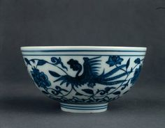 Porcelain bowl with slightly rounded sides, straight rim and high, straight foot. Decorated in underglaze cobalt blue. Three phoenixes flying among peony scrolls on the outside, and a roundel containing a floral spray in a double ring in the centre inside. Inscription on base. (Ming dynasty)