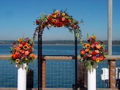 white trelles paneling decorated for a autum  Wedding  | flower decked wedding arbor on the pier share