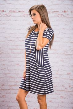 Everything I've Wanted Dress, Navy || This dress is everything you've always wanted! A cute comfy dress that you can wear any given day! It's navy and white stripes are perfect for summer with their nautical notes. We love the placement of those vertical stripes too. They create a very flattering shape! Plus, those vertical stripes lead right into pockets!