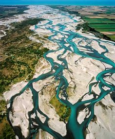 Braided river.  The separate strands of the Rakaia River wend toward the distant sea. Braided rivers form when sediment and gravel build up on the riverbed. Eventually the build-up becomes so high that the water, seeking the lowest path, begins to flow down a new channel. In this way the streams of a braided river are constantly moving across their wide bed.