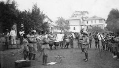 The Cameroon Schutztruppe band playing in Duala. The bandsmen all wear the 1900 khaki uniform with red fez and blue/grey puttees. Most seem to be barefooted although at least two on the right seem to be wearing German white tropical ankle boots. Note the musicians swallows nest insignia worn on the shoulders of the African bandsmen. The German NCO wears the 1896 Schutztruppe khaki uniform with a Südwester hat edged in red for Cameroon, leather gaiters and ankle boots.