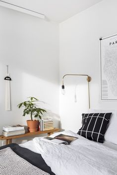 Modern light fixture coming out from wall in white bedroom with cozy details