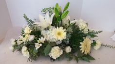 Elegant white and green centerpiece for any occasion.  White lily, white gerbera daisy, white carnations, white daisy, white hydrangea,and white freesia