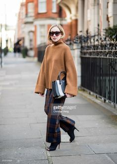 Sonia Lyson wearing brown knit, plaid wide leg pants, heels &other stories, MCM bag, Celine sunglaasses seen during London Fashion Week February 2018 on February 16, 2018 in London, England.