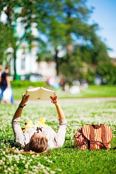 Stock Photo : Student lying on the grass and reading