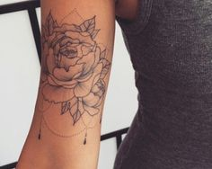 Beautiful thin-lined rose tattoo on the upper arm.