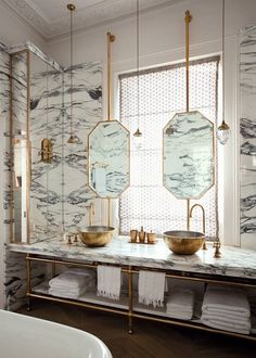 Octagonal brass mirror in front of window, Calcutta marble and brass vanity, brass vessel sinks.