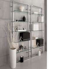 """cb2 """"Tesso Bookcase"""" Five polished clear glass shelves niched in gleaming chrome scale the wall to dramatic heights.  Modern étagère reflects light, looks light—but plated metal tube frame wallmounts super sturdy."""