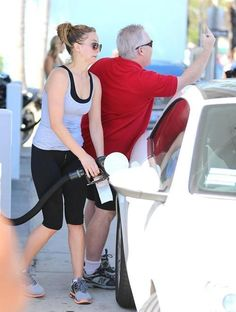 Jennifer Lawrence pumping gas while her Dad flips off the paparazzi. Priceless!
