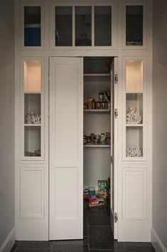 Walk-in pantry with bi-fold doors flanked by built-in display cabinets #kitchen