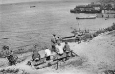 Gallipoli: Through the Soldier's Lens   The Public Domain Review -- Four unidentified men using a latrine high above the beach at Anzac Cove (1915)