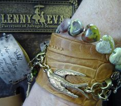 L & E Natural Embossed Leather Wide Band with Antique Brass Bird Pendant. Stone Heart Bracelet and Key Charm Handcrafted by Nova Leigh....only available @ PJ's!