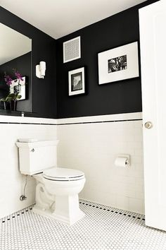 Un soubassement blanc et un mur peint en noir avec des cadres, une association déco parfaite pour embellir le petit coin.