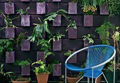Pintado com tinta roxa, o painel desenhado pelo escritório Casa 14 possui blocos de concreto virados, que formam os vasos com plantas pendentes. A moradora teve a ideia ao ver um projeto parecido, quando passava por uma movimentada avenida de São Paulo