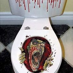 Halloween or scary party decoration of a terrible toilet topper picturing a blow full of bloody water and a mutilated Zombie reaching out of the toilet bowl. This terrible Halloween decoration will stick to the top of your toilet lid and scare the hell out of your friends