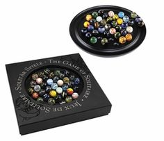 Authentic Models Solitaire Di Venezia, Marbles.  The game of Solitaire is reputed to have been invented by a nobleman confined in the Bastille prison during the early years of the French Revolution. The game is played with 36 marbles. The object is to eliminate all but one marble, which should ideally end up in the center of the game board. Individually hand blown glass marbles, full of color, against a solid ebony board. Art in itself, functional and fun as solitaire.