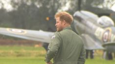Prince Harry dons a khaki flight suit and shows off his rugged ginger beard at an RAF flypast event.