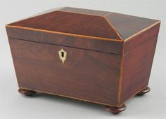 An early 19th century mahogany tea caddy, of sarcophagus shape with boxwood stringing, the hinged cover to a pair of lidded compartments with turned bone handles, to a shaped escutcheon on turned disc feet, 6in (15cm) h, 8.5in (21.5cm) w, 6in (15cm) d.  Woolley & Wallis