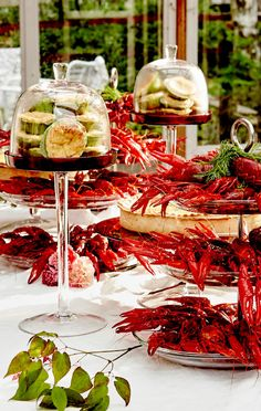 Pöytä, johon on katettu vadeille rapuja ja erilaisia piiraita.