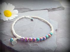 Sweetest dainty Rainbow Hematite Gemstone  solid Sterling Silver Stacking/Layering Bracelet. Minimal size - Maximum sparkle.   Dainty bracelet with a teensy heart charm and Hematite dangles. Great for stacking. The last photo is to give an idea of size - you will receive one bracelet as in this listing.   * All metal SOLID Sterling Silver,not plated   * Genuine faceted Hematite Gemstone Beads ( rainbow plated) (4mm) and Sterling Silver beads   * Teensy Sterling heart charm and Hematite d...