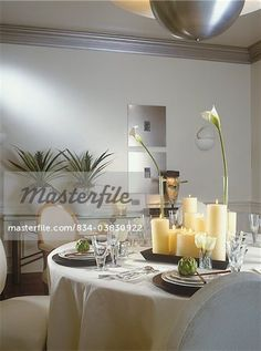 DINING ROOM  - Contemporary, eclectic. Tablecloth, , glasses, artichokes, tray of various different height candles, calla lilies, glass side table with two ceramic white pots with pinneapple plants, silver framed artwork, silver molding, white walls and dado, African mask, Kidogo,chopsticks, Louis style chairs  – Image © Sheltered Images / Masterfile.com: Creative Stock Photos, Vectors and Illustrations for Web, Mobile and Print