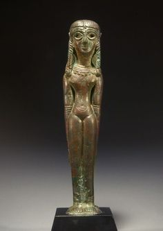 SYRO-PALESTINIAN BRONZE NUDE GODDESS Standing with her braceleted arms at her side and wearing a broad collar. Her centrally parted, long, straight hair with two braids framing the face and another down the center at the back of her head. Late 2nd Millennium BC